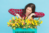 Charming female florist sorts out tulips in the box, selects them for the future flower arrangement - 205935401