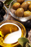 Bottle virgin olive oil and oil in a bowl with some olives - 205938293