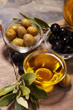 Bottle virgin olive oil and oil in a bowl with some olives - 205938294