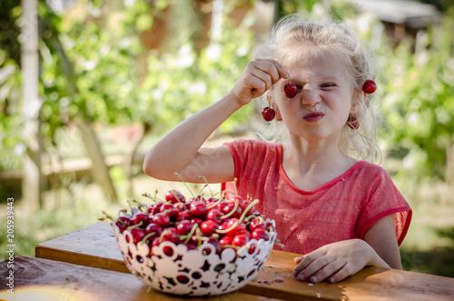 Foto Murales child eating cherry fruit