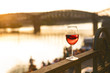 Quadro Glass of red wine on a railing with sunset in a Prague city. Concept of free time in the city and drinking alcohol.