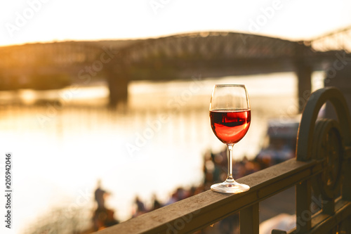 Foto Murales Glass of red wine on a railing with sunset in a Prague city. Concept of free time in the city and drinking alcohol.