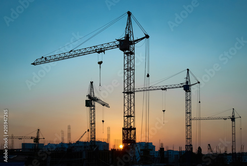 Fototapeta Industrial landscape with silhouettes of constraction cranes on dramatic sunset background