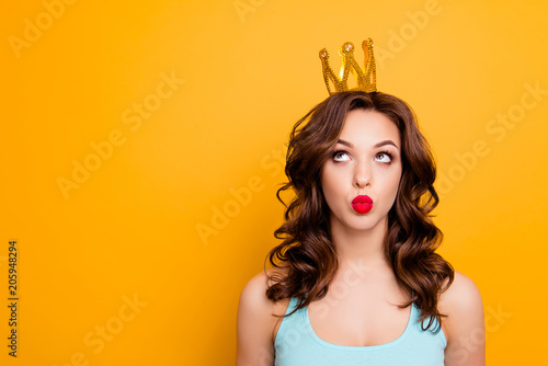 Leinwanddruck Bild Portrait with copyspace empty place of funny stupid girl looking at crown on head with eyes sending kiss with pout lips isolated on yellow background advertisement concept