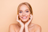 Nude, charming, pretty, cute, toothy cheerful girl with beaming smile perfect face skin after detox, vitamins, collagen holding hands on cheek, isolated on beige background, wellness wellbeing concept