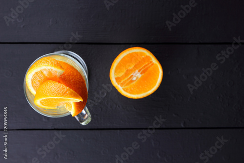 Pieces of tropical fruits in a glass. Fruit cocktail on a black background. Sliced orange, kiwi cubes, slices of pineapple in a glass bowl. Citrus fruits on a dark background