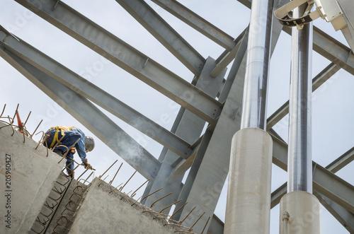 Welder soldering metal girders in a structure high above