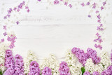 Colorful lilac flowers border on white wooden background. Top view, copy space. Spring background. Greeting card.