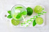 Summer limeade in a glass. Top view on a marble server against a bright background.