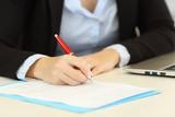 Closeup of an executive hands filling a form on a desktop - 205970441