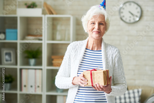 Waist up portrait of cheerful senior woman wearing Birthday cap posing at home, looking at camera and holding gift box, copy space