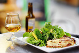 Traditional French food: quiche lorraine and fresh salad leaves with glass of beer on background - 205973453