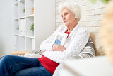Side view portrait of devastated senior woman lovingly hugging framed photograph of her husband sitting at home alone in armchair by brick wall photo in frame by me . - 205975008