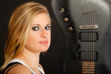 Blonde woman holding electric guitar, black background - 205978416
