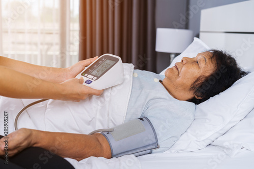 nurse checking blood pressure of a senior woman on bed