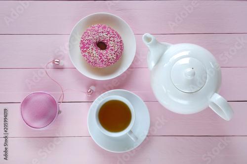 Poranna herbata leżała płasko. Biała filiżanka z herbatą, biały czajniczek, różowy pączek, różowe słuchawki na różowym tle drewniane deski. Poranna herbata w różowych i białych pastelowych kolorach. widok z góry