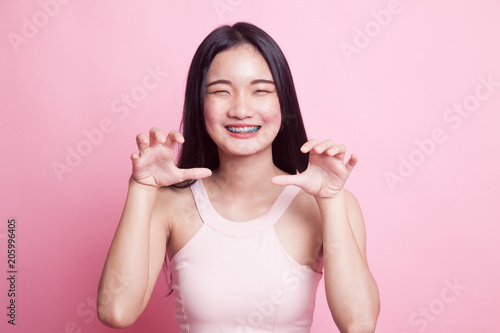 Young Asian woman with spooky hands gesture.