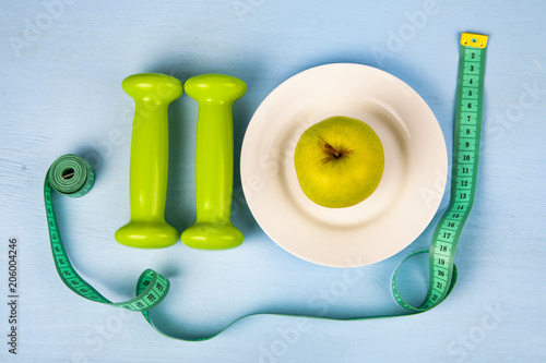 Apple na talerzu, hantle i taśma miernicza