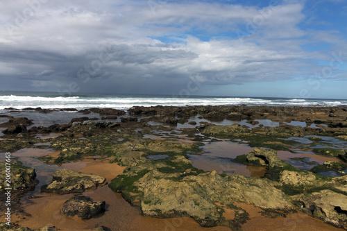 Rocky Beach Waves and Ocean Against Blue Cloudy Skyline