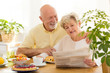 Quadro Happy senior woman reading newspaper during breakfast with smiling husband