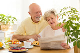 Happy senior woman reading newspaper during breakfast with smiling husband - 206009241