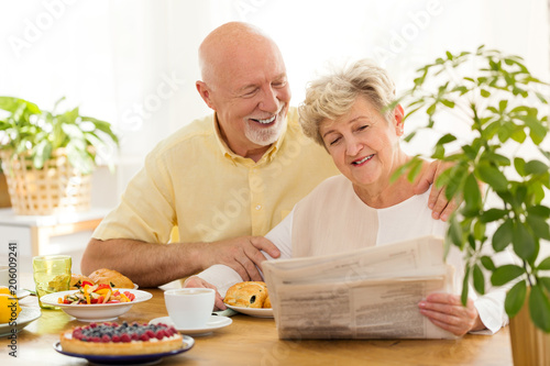 Foto Murales Happy senior woman reading newspaper during breakfast with smiling husband