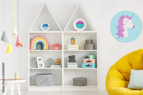 Rainbow, telephone and boxes on white shelves, unicorn poster, lamps and yellow pouf in a child's room interior