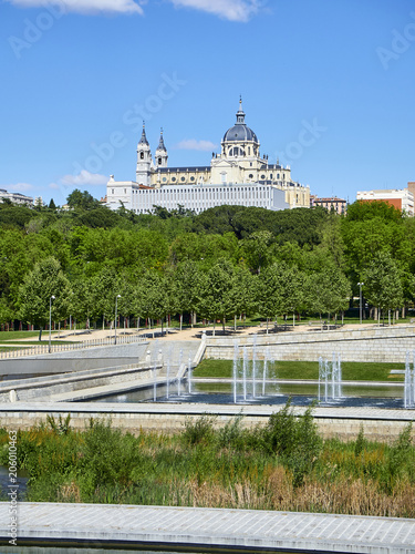 Green spaces of Madrid Rio with the Almudena Cathedral in background.