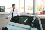 Fototapety Handsome mature businessman getting in taxi