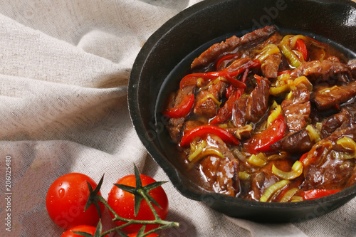 fried  meat and vegetables in a frying pan with tomatoes on textile background