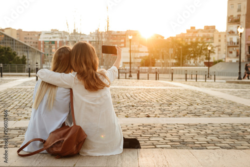 Foto Murales Back view photo of two friends women