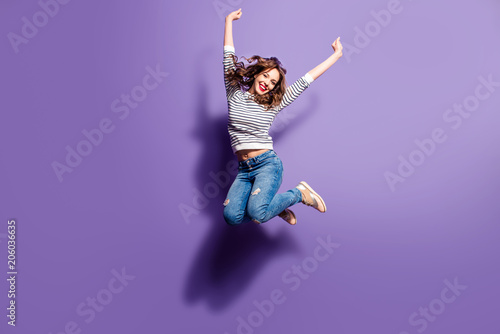 Leinwanddruck Bild Portrait of cheerful positive girl jumping in the air with raised fists looking at camera isolated on violet background. Life people energy concept