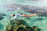 woman enjoying  the snorkeling with a water proof camera, in Koh Lipe island