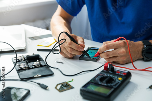 smartphone repair - technician check the the phone with multimeter