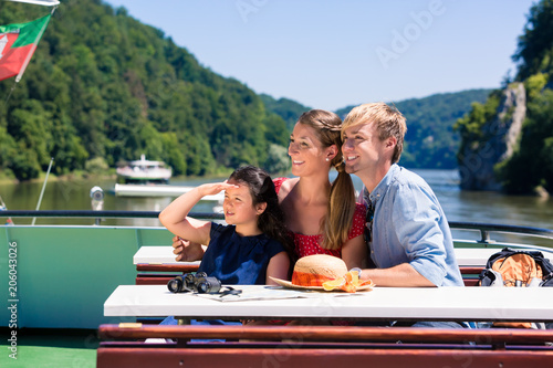 Fototapeta Happy family on river cruise looking at mountains from ship deck