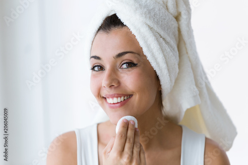 Pretty young woman is cleaning her face while looking in the mirror in the bathroom.