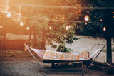 stylish travel hammock under retro lights in summer forest park. resting, camping and relaxing outdoor, summer vacation and holiday. space for text. wanderlust and adventure. - 206045231