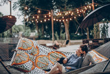 stylish hipster family cuddling and relaxing in hammock under retro lights in evening summer park. rustic man and woman embracing and resting in forest. space for text. atmospheric moment - 206045285