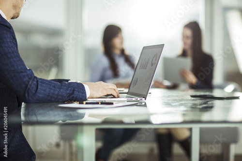 Wall mural financial managers working on laptop with financial data at the workplace in a modern office