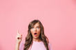 Closeup photo of excited woman with long curly brown hair pointing finger upward at copyspace with interest, isolated over pink background