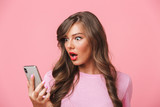 Closeup image of puzzled woman having beautiful long hair looking at smartphone in hand with bulging eyes, isolated over pink background - 206045673