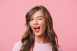 Leinwanddruck Bild - Image closeup of young attractive woman 20s with long curly hairstyle and seductive look winking at camera with smile, isolated over pink background