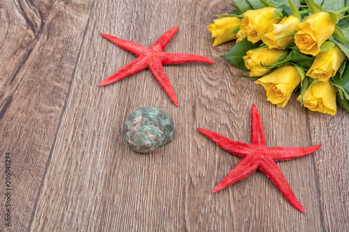 Foto Murales Concept of starfish and tulips on a table