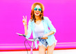 Leinwanddruck Bild - Young woman with bicycle over colorful pink background