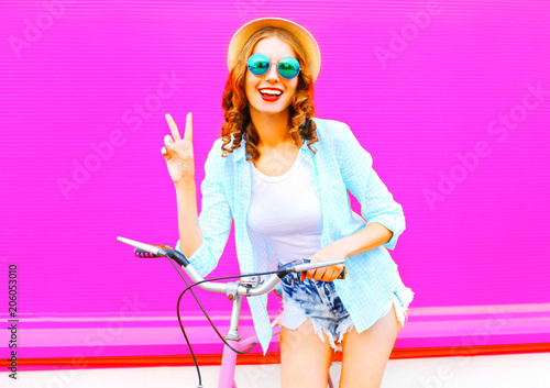 Leinwanddruck Bild Young woman with bicycle over colorful pink background