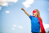 Funny little girl playing power super hero over blue sky background. Superhero concept. - 206053259
