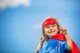 Funny little girl playing power super hero over blue sky background. Superhero concept. - 206053429