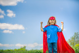 Funny little girl playing power super hero over blue sky background. Superhero concept. - 206053494