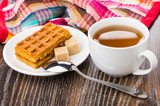 Waffles, sugar cubes on saucer, cup of tea, spoon - 206063653