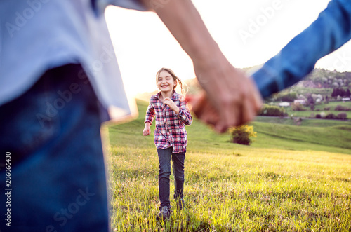 A small girl with her senior grandparents having fun outside in nature.